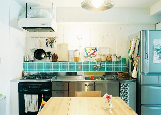 シンプルなステンレスキッチンには、グリーンのタイルを合わせて。