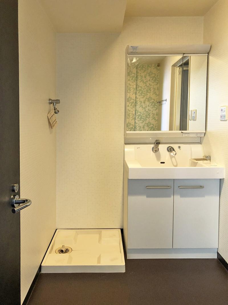 鏡越しに柄クロスが見える洗面スペース