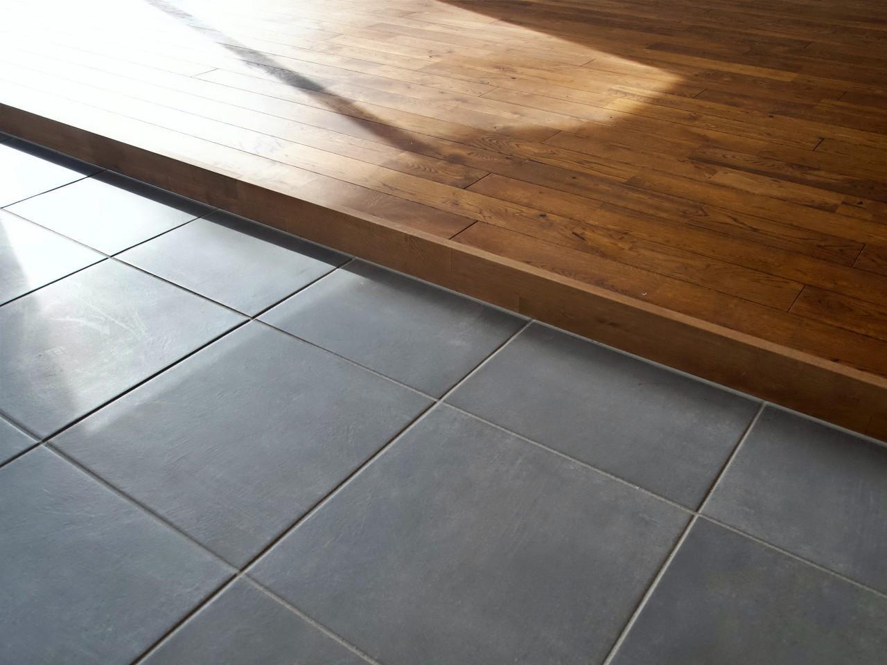 磁器タイルの床と無垢フローリングの小上がり
