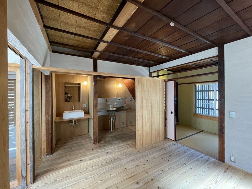1階 室1。キッチンはパーテーションで緩く仕切られている