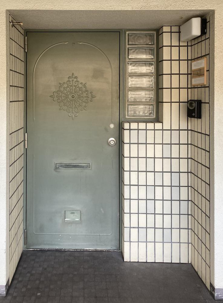 淡いグリーンの玄関扉とガラスブロックのデザインが異国の雰囲気