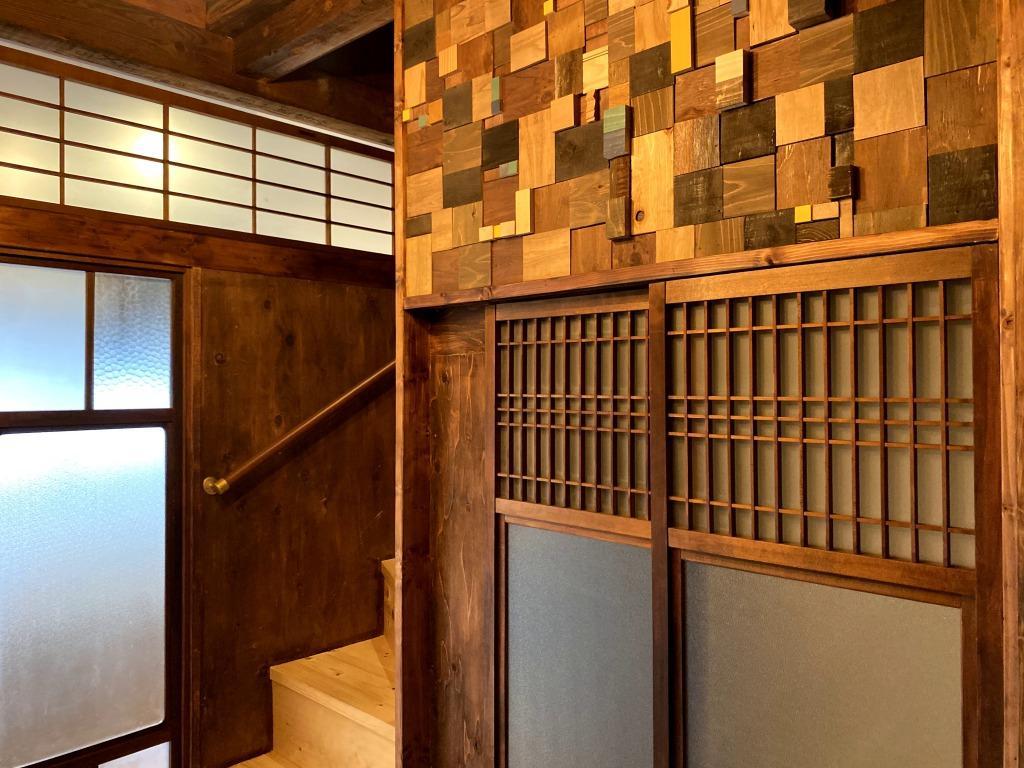 長屋の趣を感じさせる建具、上部は端材を組み合わせた壁面