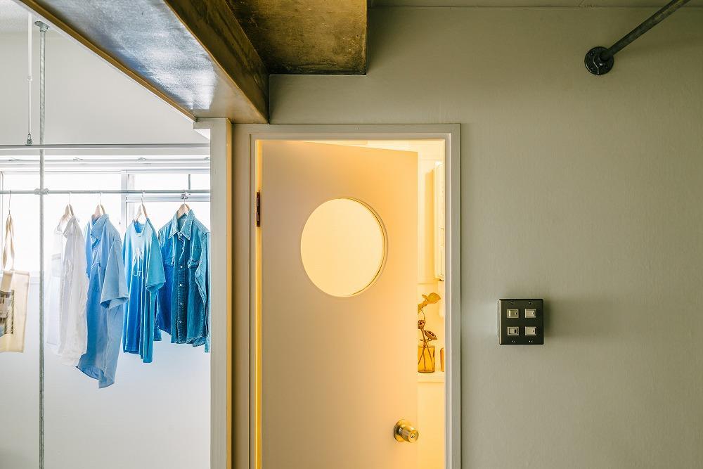 既存再利用のトイレのドア、丸い窓が可愛らしい。
