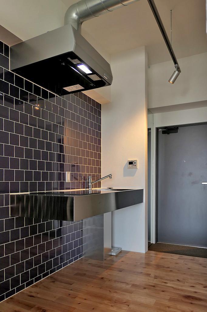 ステンレスキッチンと濃紺のタイル、ダクトレール照明。