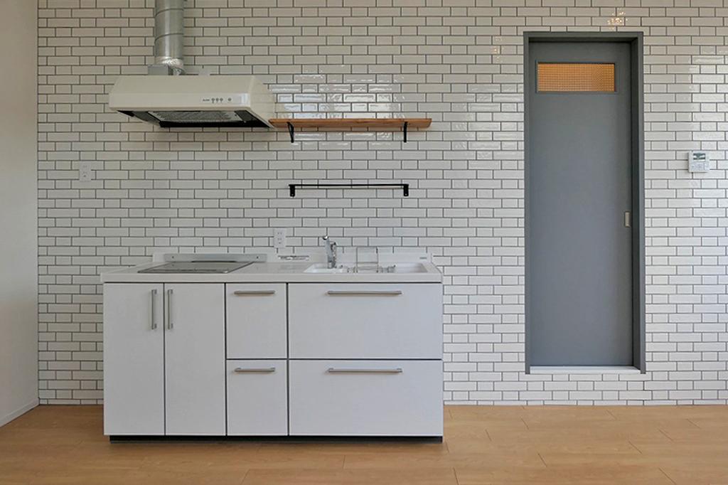 白のキッチンと白のタイル、グレーの建具が素敵