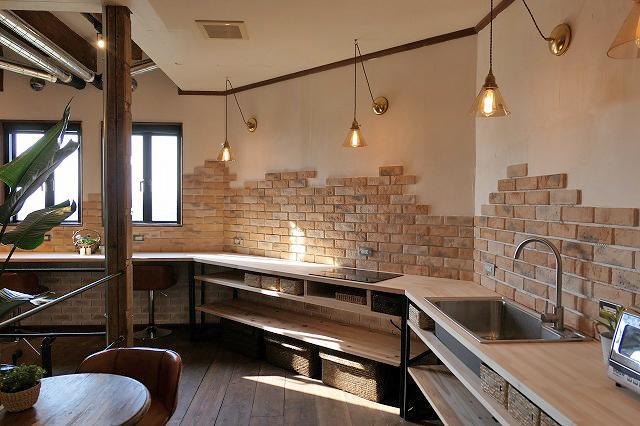 漆喰とレンガの壁、無垢の床、素材にこだわったキッチンです。
