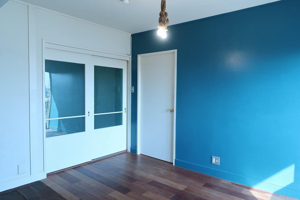 リビングは目の覚めるような青い壁。床はチェリーの無垢フローリング。