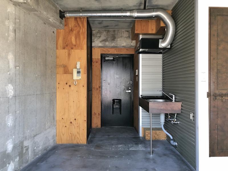 むき出しのコンクリートと構造用合板で構成された室内