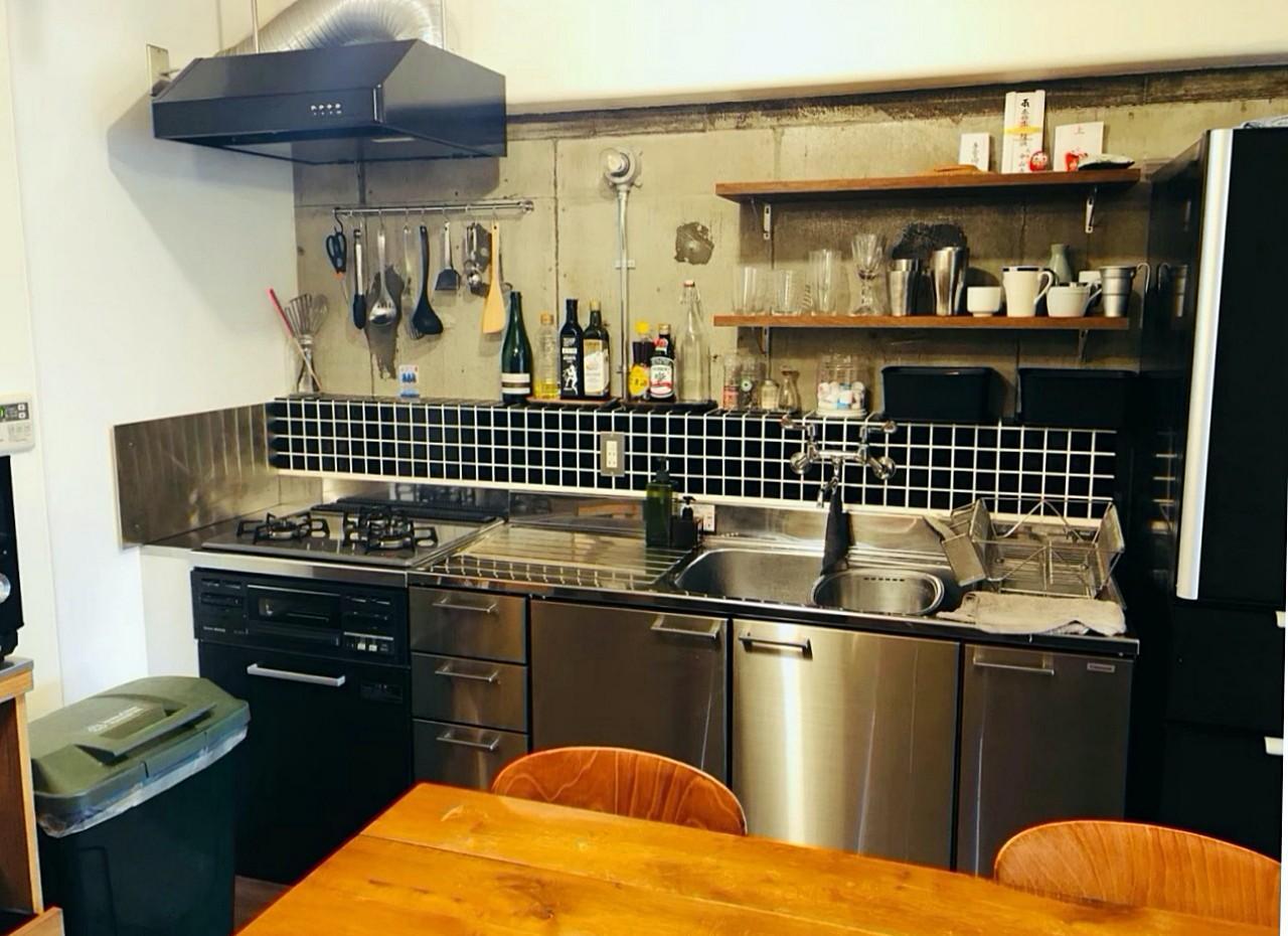 渋めのタイルとステンレスのキッチンが骨太な雰囲気