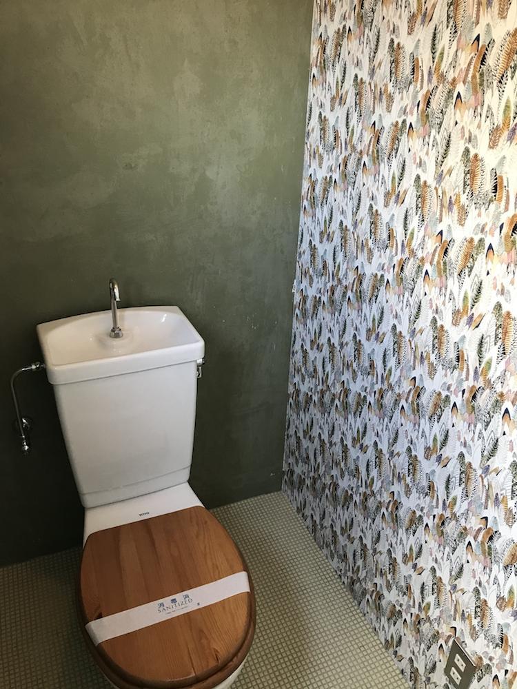 トイレは床タイル×柄クロス×木製便座という味わいが詰まった空間