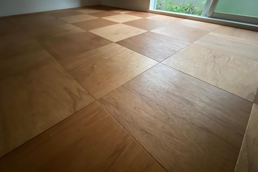 ヤスリがけした合板を四角くカットして並べた床