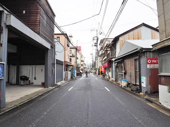 建物の前通り。歩いてすぐのところにスーパーがあり、人通りはぼちぼち。下町感のある街並み