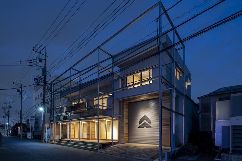 夜は照明で建物が浮かび上がります、シャッターにペイントされた桃と山の企業ロゴがライトアップされ目立っています