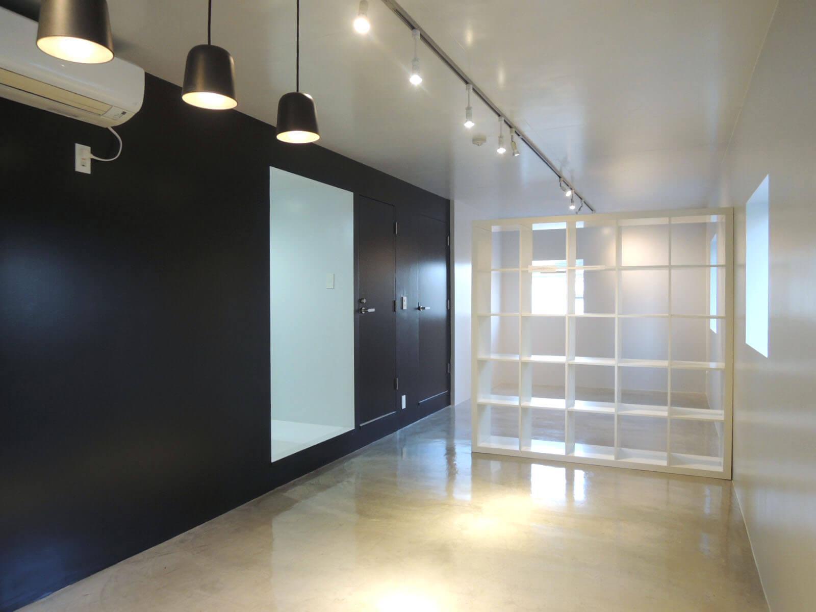 輝くモルタルの床、黒壁に浮かぶ白い穴はキッチン