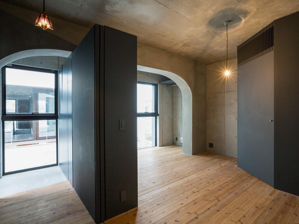 2階の寝室。打ち放しの壁にダークグレーでまとめられた建具が無機質な雰囲気。リビングとギャップがあって良い