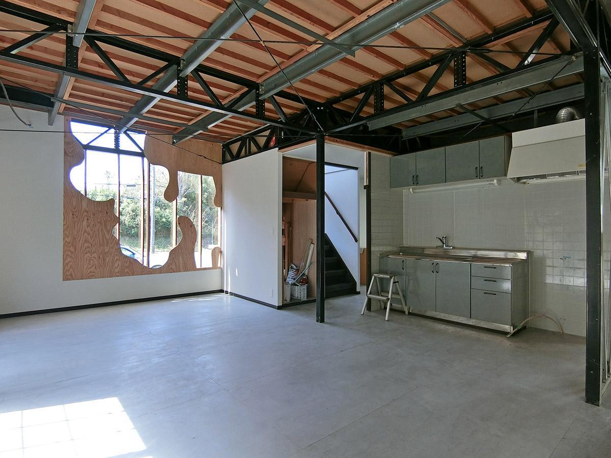 共用棟:キッチンとリビング。今後テーブルなどの家具が入る予定。開放的な天井、鉄骨の柱が倉庫のよう
