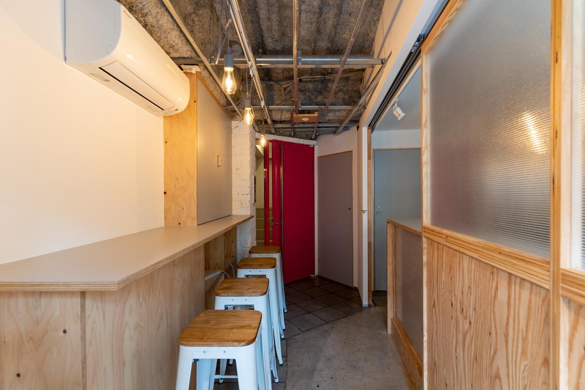 店舗区画を抜けた先の赤いドアが2階より上に上がるエントランスです