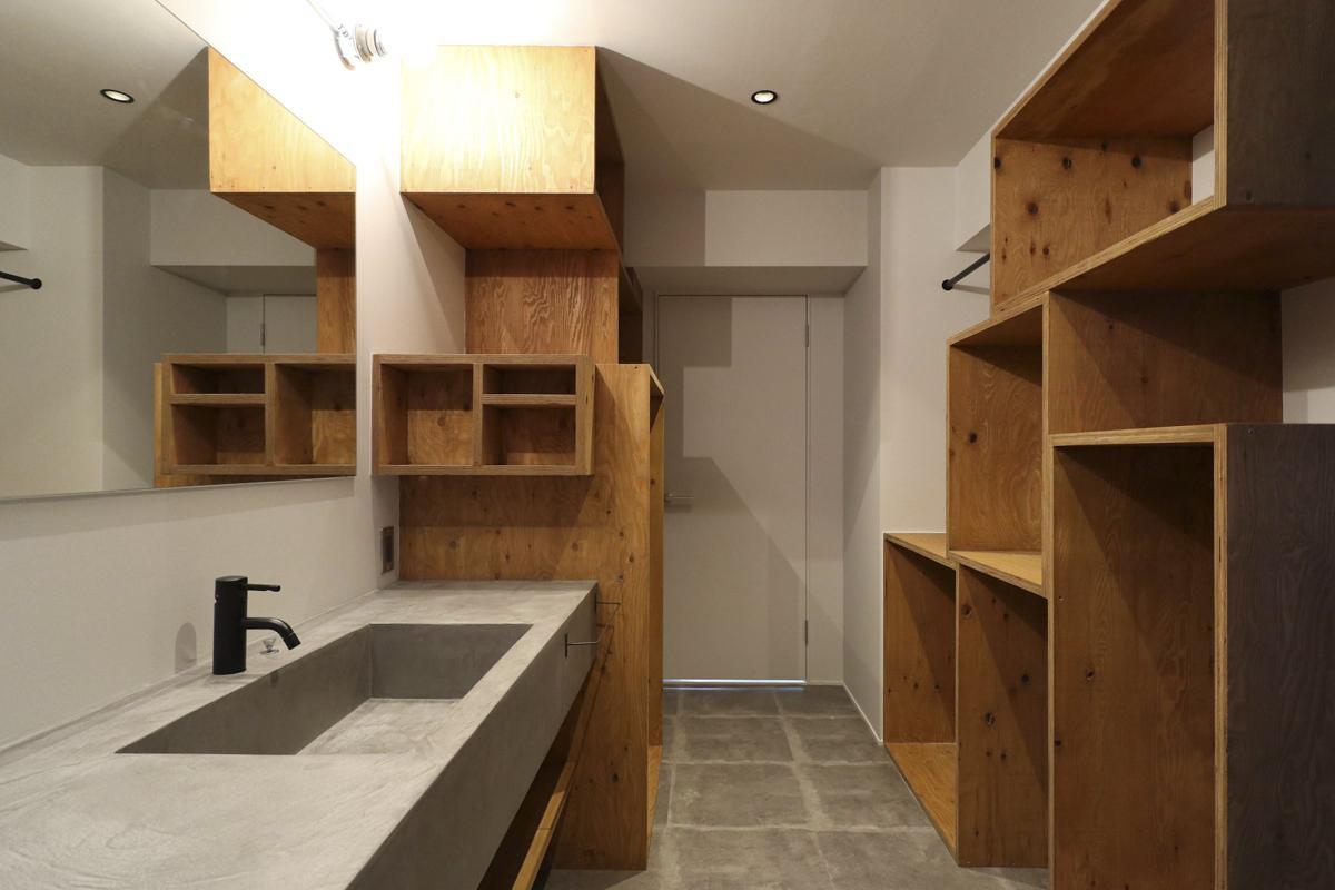 モールテックスの洗面台と、造作収納棚が印象的な洗面室。床はフロアタイル