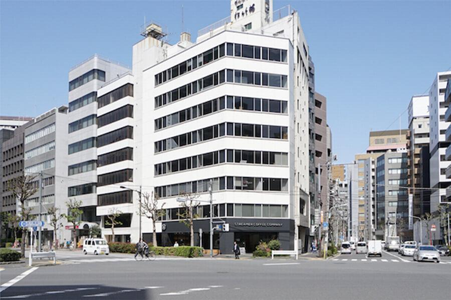 外観。写真正面の建物の左隣が、本物件のある建物です