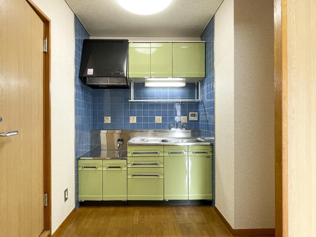 ブルーのタイルと緑のキッチンがレトロで可愛らしい