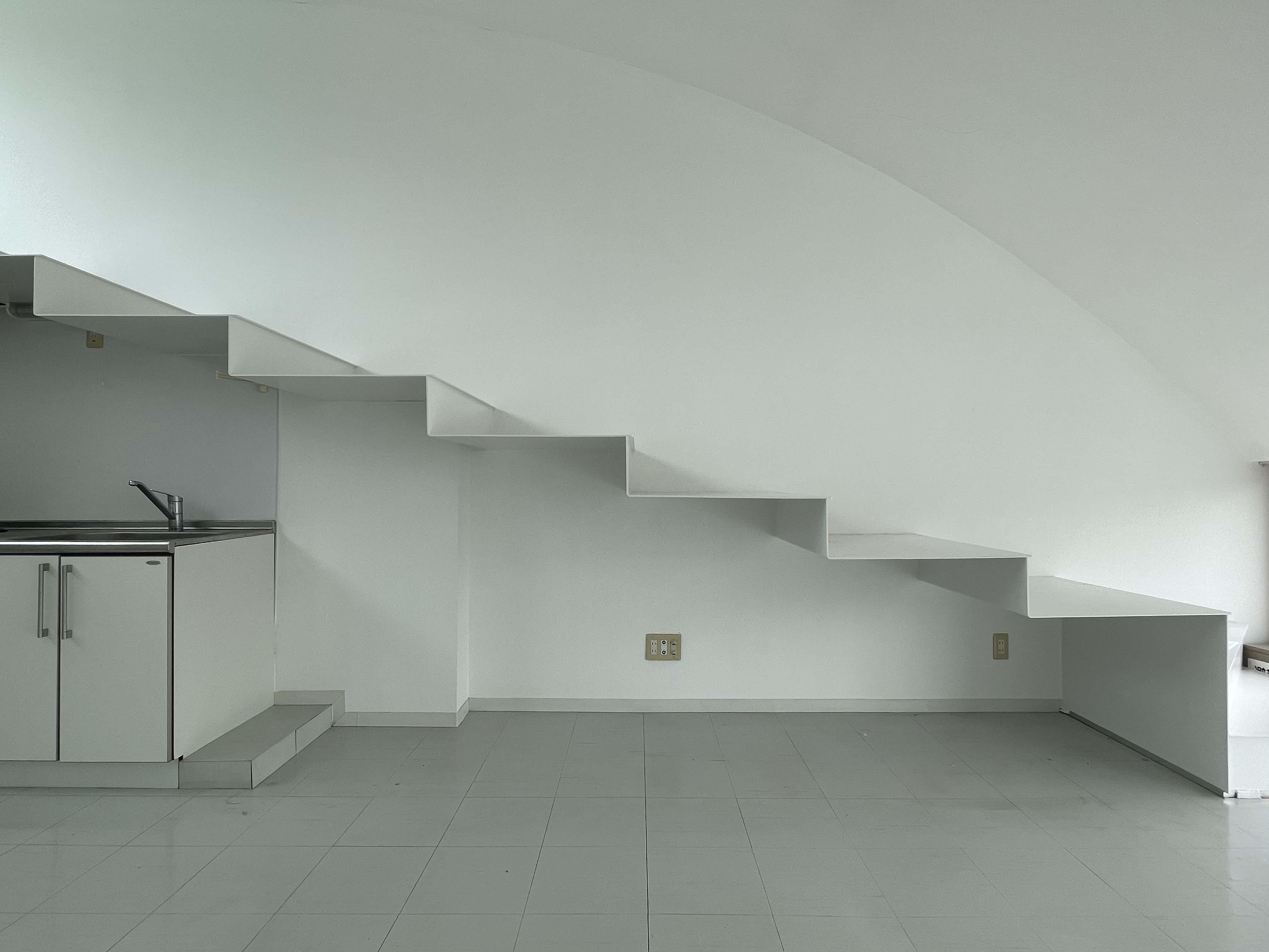 階段が壁から生えているよう。階段下に物を収納できます