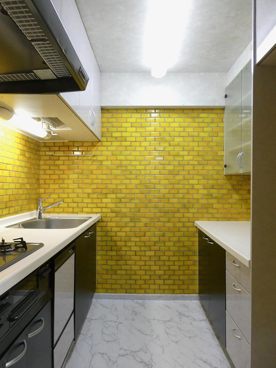 キッチンは黄色いタイル張り。収納もたっぷり