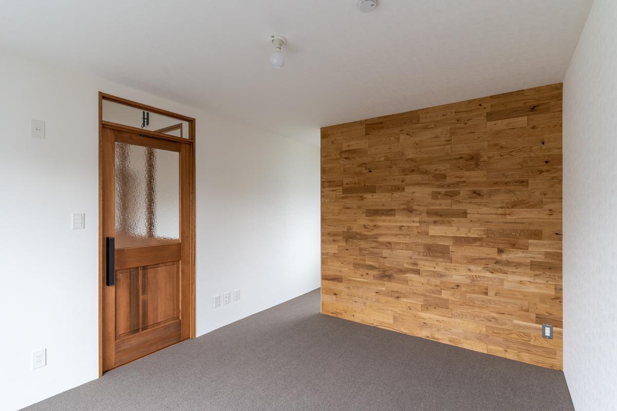 主寝室はカーペットの床に無垢フローリングの壁