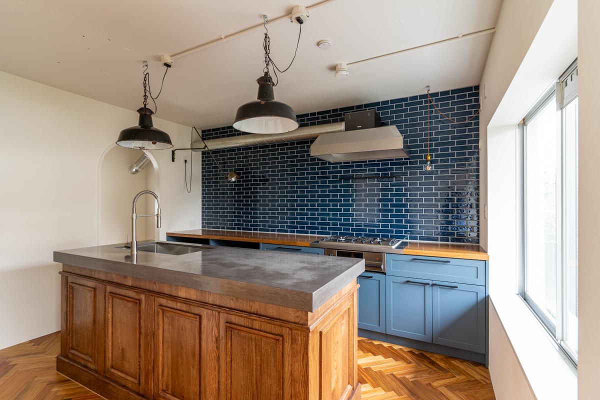 モールディングで縁取られたカウンターと、造作キッチンはタイルと合わせたブルーグレー