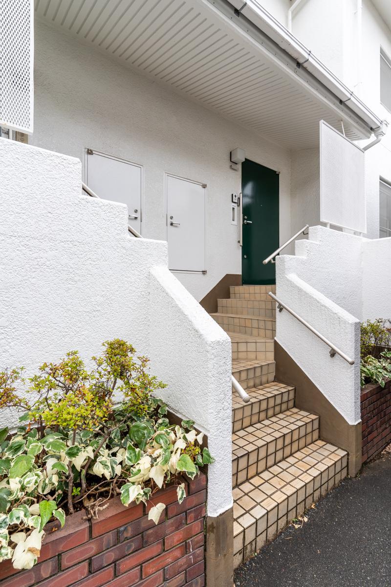 階段を数段上った先の緑のドアがこの区画の玄関です