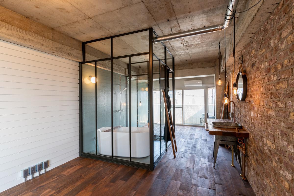 ワンルームをガラス張りのバスルームが仕切っています