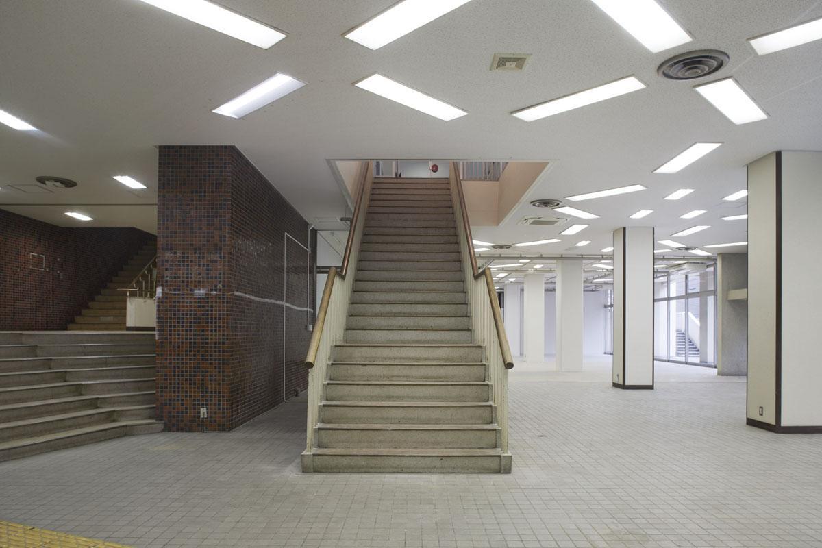 【1F】イベントホール:エントランスをくぐると、開けた大空間の中央に階段が現れます
