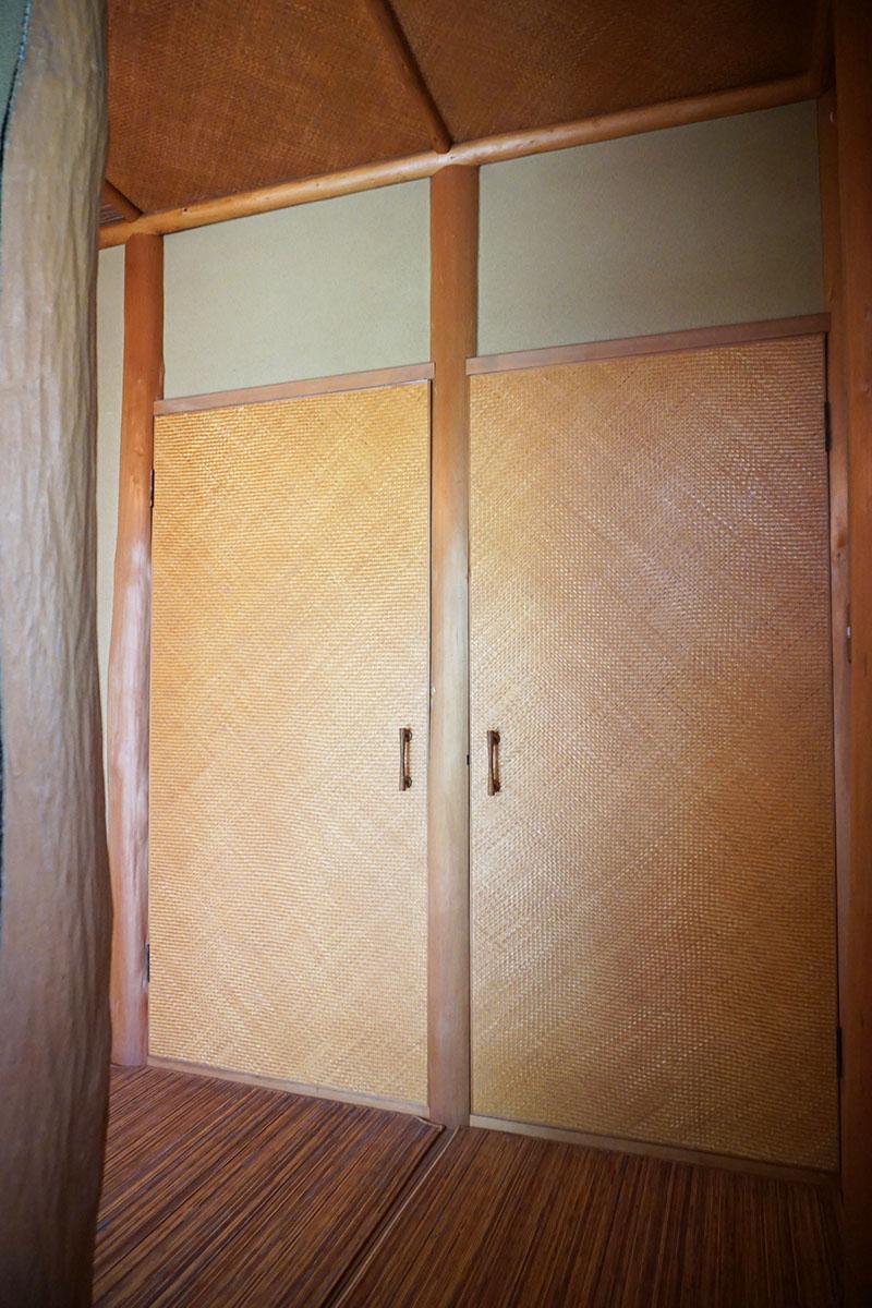 収納、戸には竹を編み込んだシートを用いている。経年変化もいい感じ。右がトイレ、左がキッチンのドア