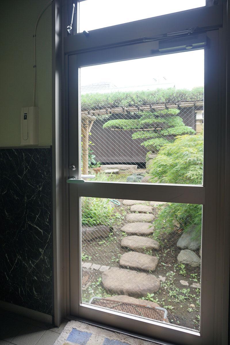 マンション共用廊下の奥にある、庭への入り口。鍵付きなのでマンションの入居者は出入り不可