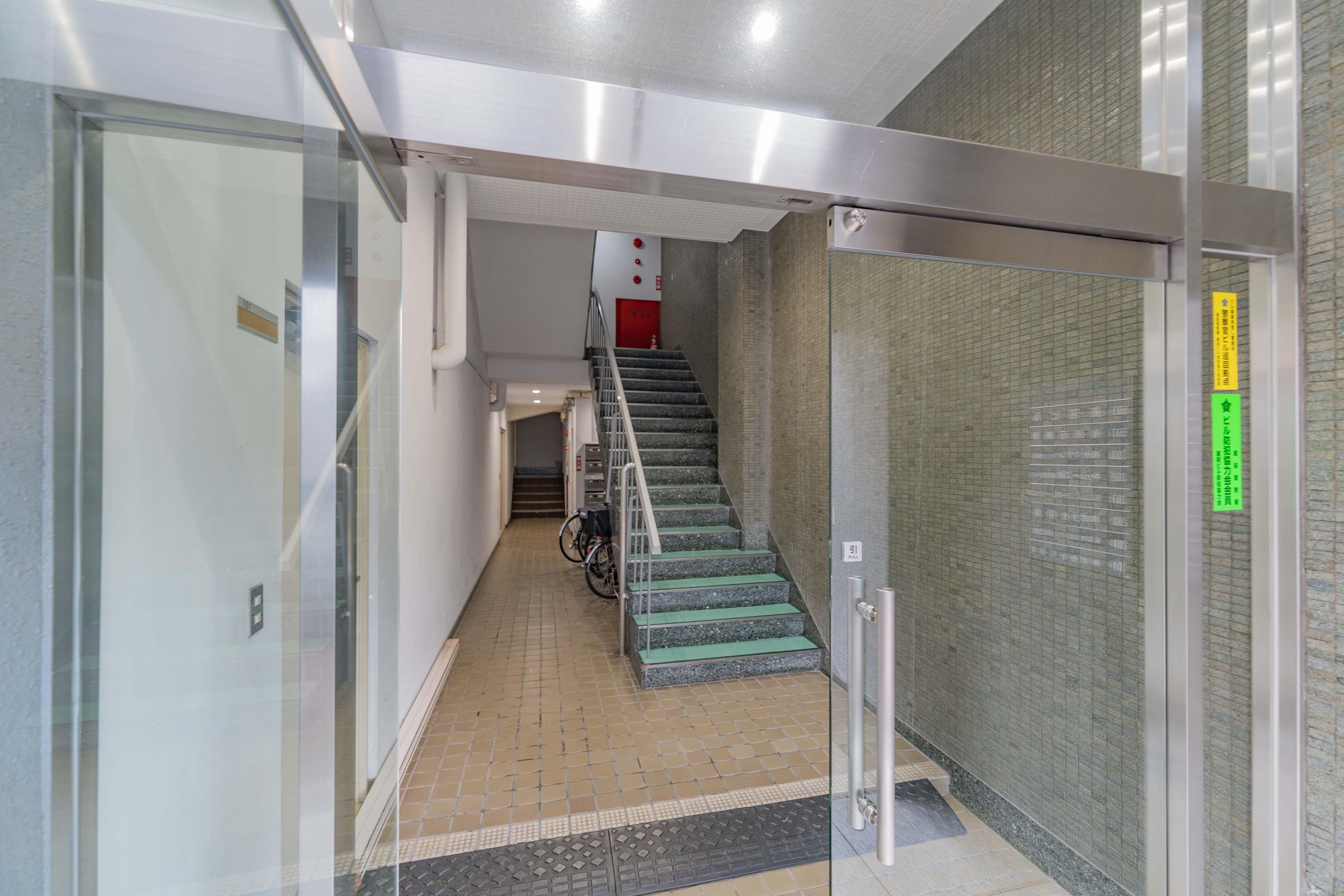 エントランス。階段の奥にエレベーターがある