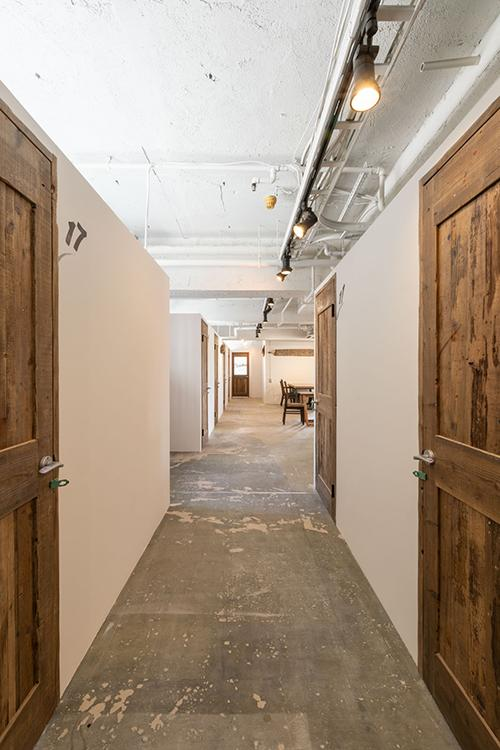 個室が並ぶ。床はコンクリートがあらわされた無骨な仕上げ
