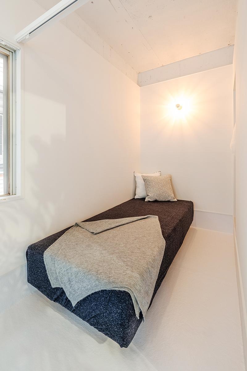 カーテンレールで間仕切りされたコンパクトな寝室