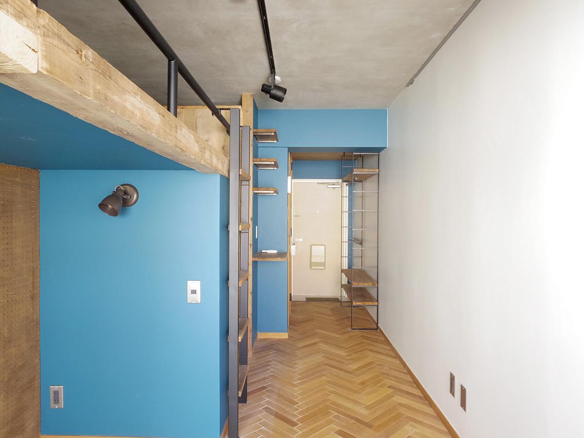 天井はモルタル仕上げ、床は無垢材をヘリンボーン張り、壁はブルーと白に塗装されている