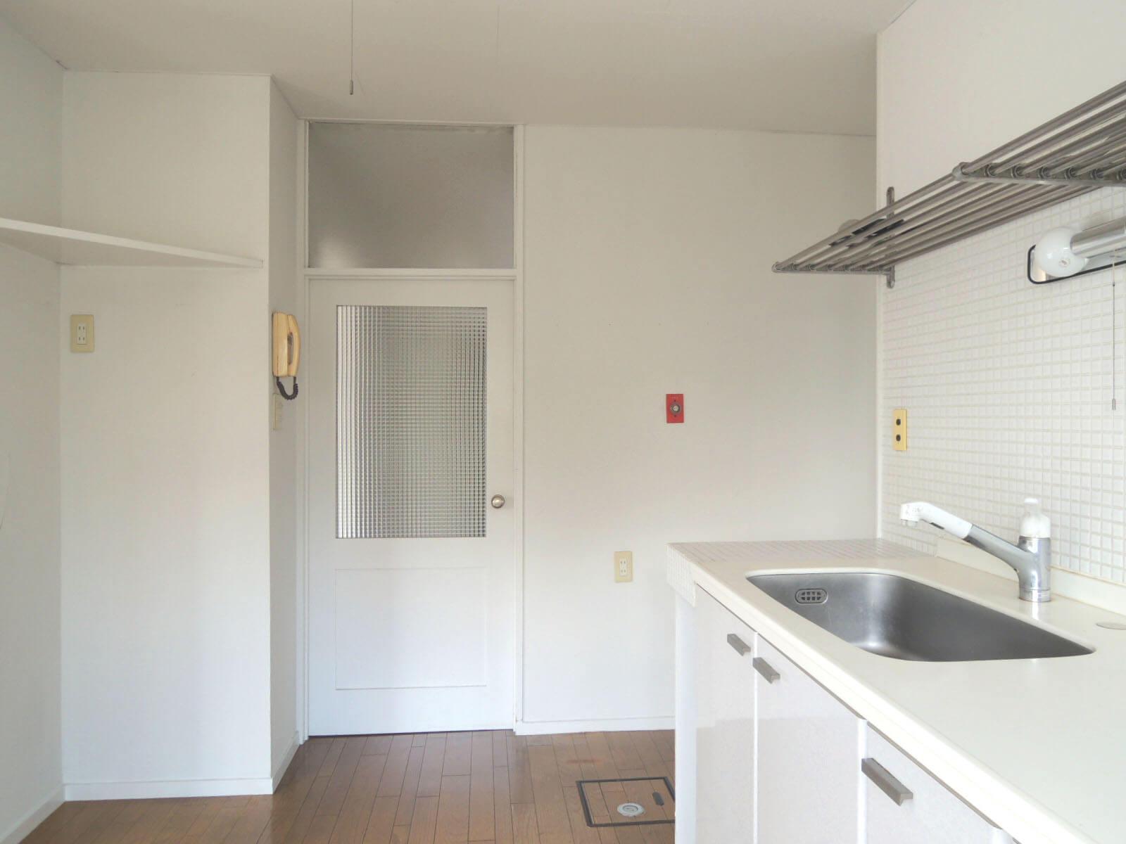 障子戸のほかにこのドアからも玄関へ、左角が冷蔵庫置場