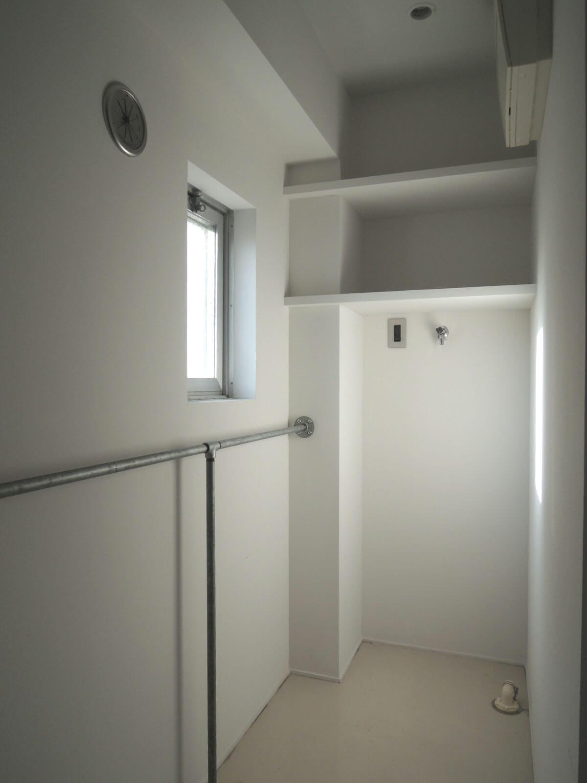 光が射す洗濯機置場、壁付けのパイプが何かと便利
