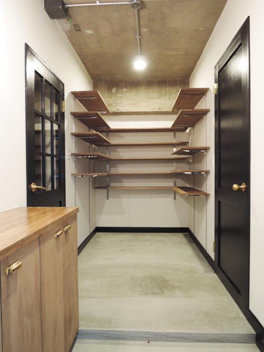 玄関の収納。床はモルタル。扉は黒く塗装され、こってりめなデザイン。