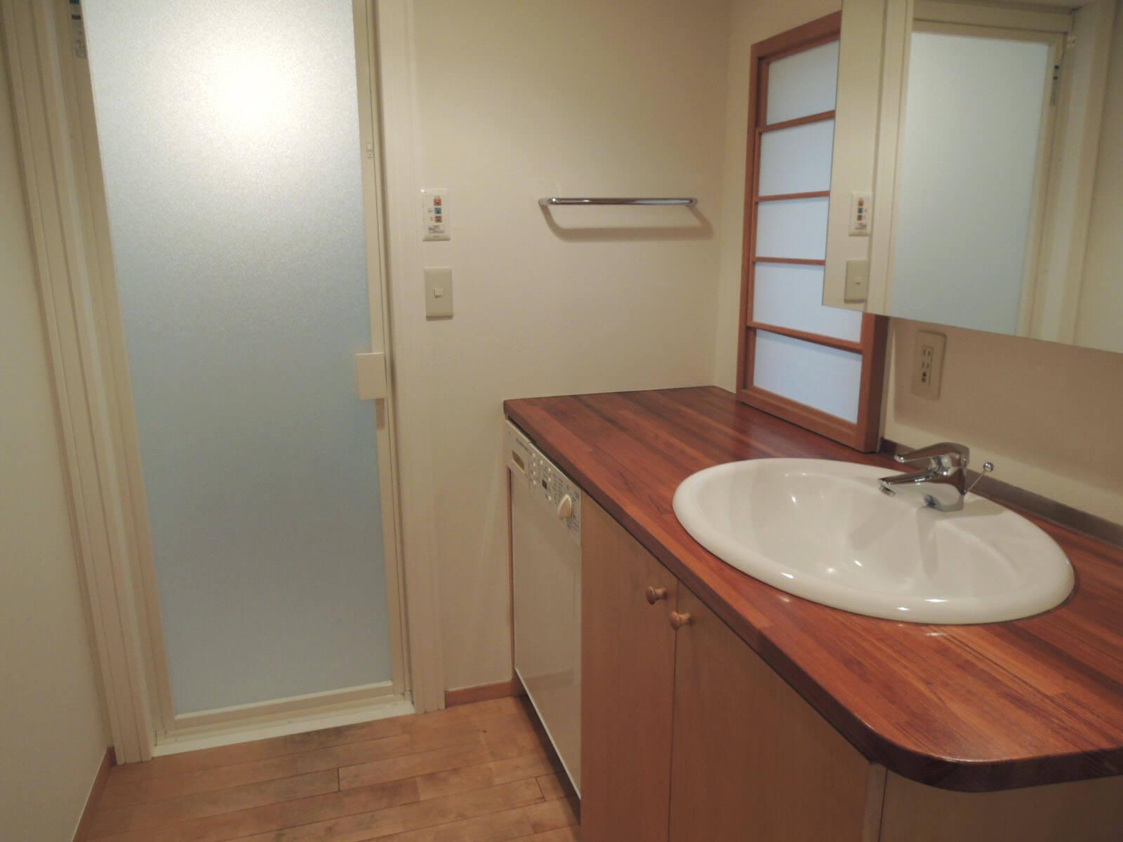 洗面台も木の天板に。洗濯機は残置物。