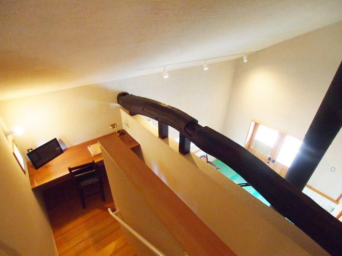 リビングから階段部分を見下ろす。階段の踊り場には書斎になりそうなスペース。右手は土間の吹き抜け。
