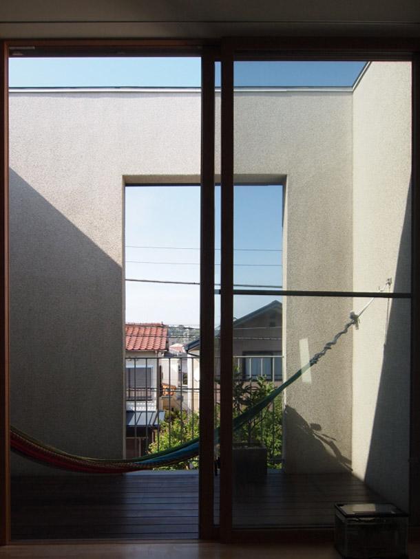 バルコニーは壁に覆われて籠り感がある。北側の窓なので、壁に光を反射させ、室内を明るくさせている。