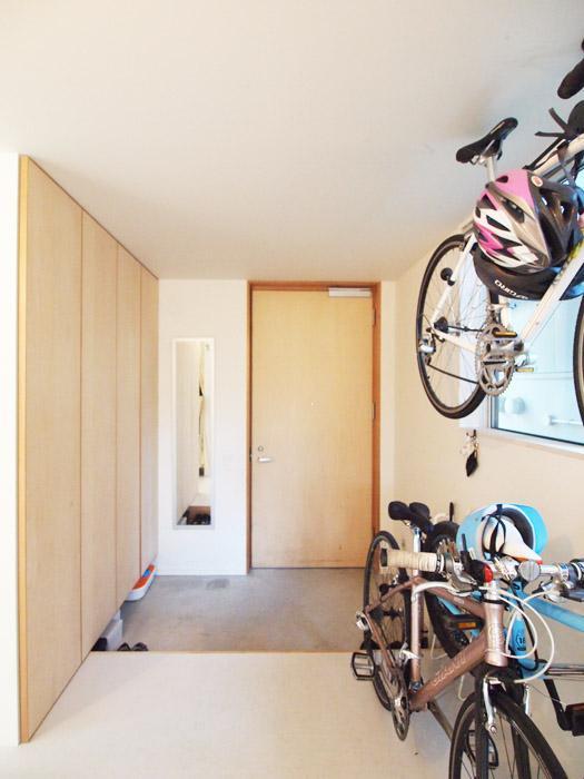 玄関は自転車やベビーカーなどが置ける。シナの素材が優しい。