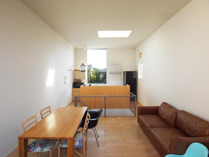 大きなビワの木が見えるキッチンの窓がかっこいい。トップライトからも光が差し込み明るい。中央に階段。