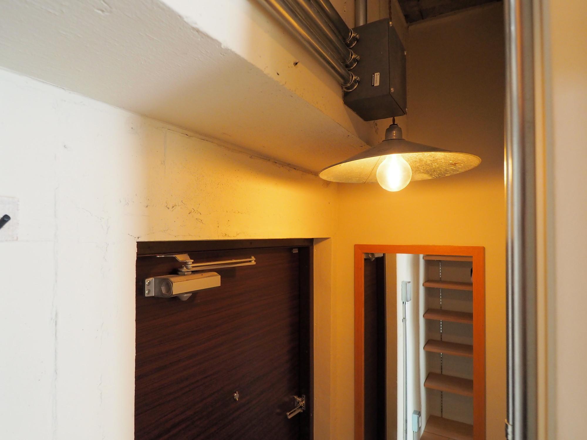 シェードと鏡が設置された玄関