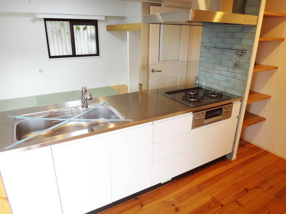 ブルーのタイルが素敵なオープンキッチン。サイドの収納は何かと重宝しそうです。