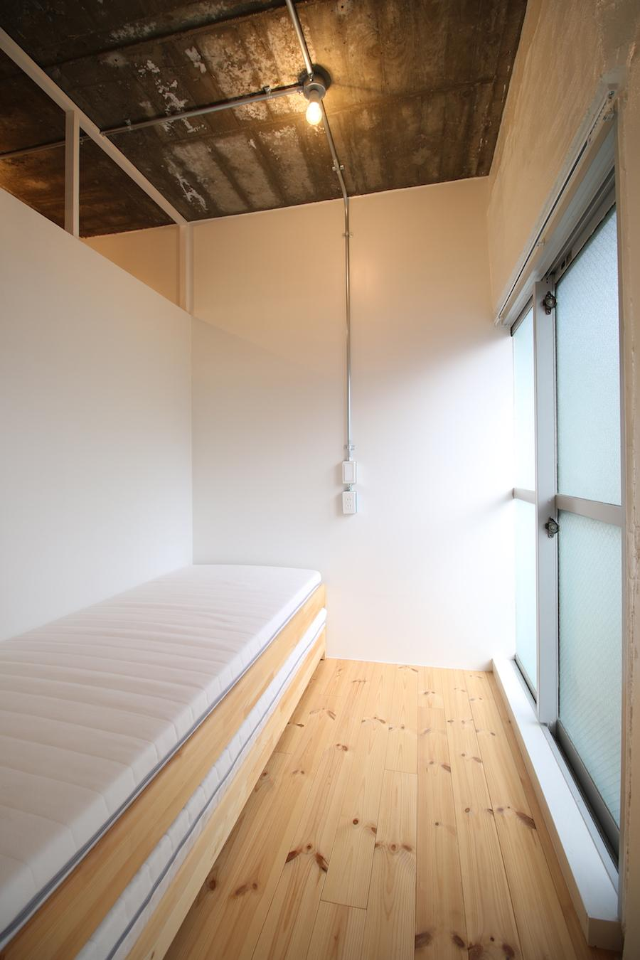 写真のベッドはシングルよりもやや幅が狭いタイプのもの。ダブルもぎりぎり収まる広さ(301号室)