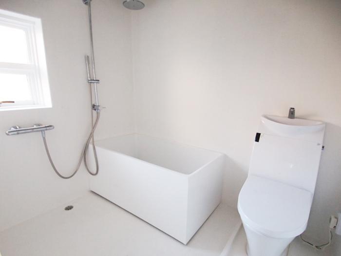 真っ白なバスルーム。トイレと浴槽はシャワーカーテンで区切れる