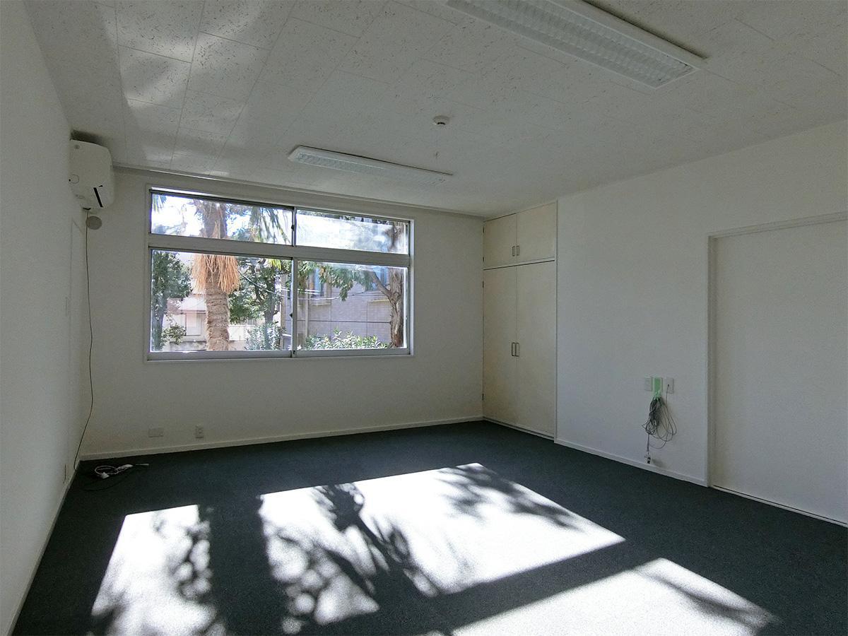 木漏れ日が入る明るい部屋。窓からは敷地の緑が見える
